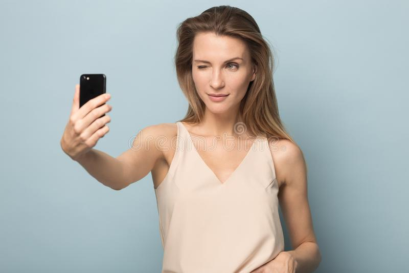 Smiling woman make self-portrait picture in studio. Smiling millennial woman isolated on blue studio background make self-portrait look at camera make victory royalty free stock images