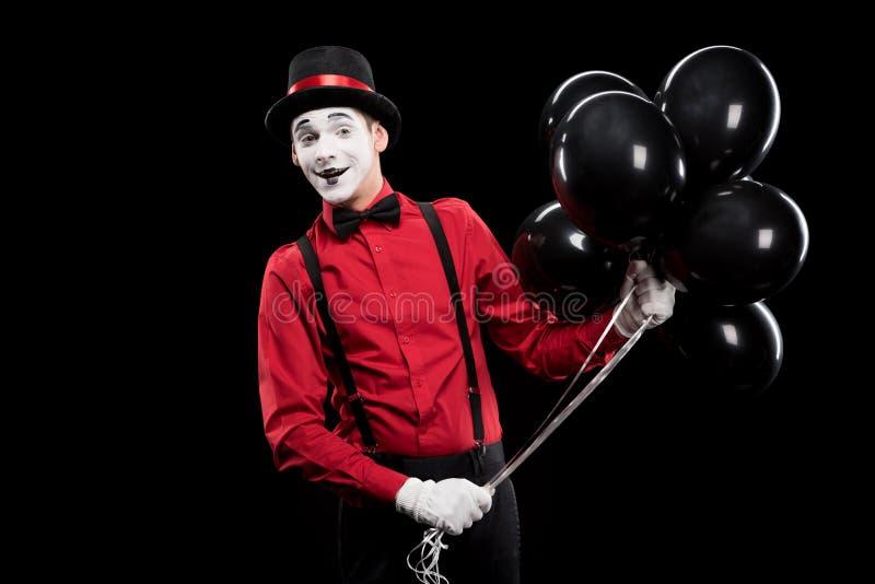 smiling mime holding bundle of black balloons stock photo