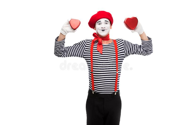 smiling mime holding heart shaped gift boxes stock photo