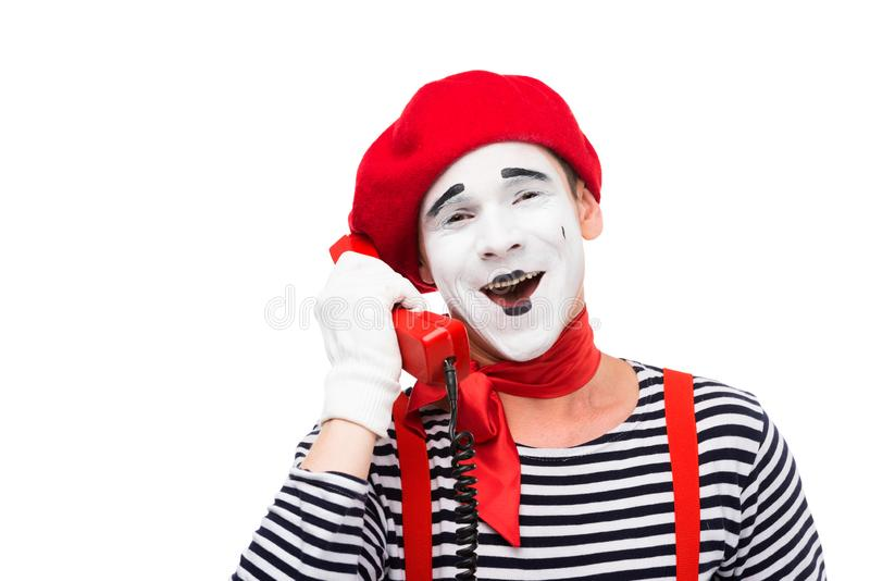 smiling mime talking by stationary telephone stock photography