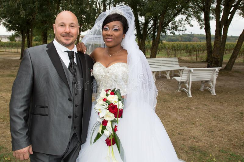Smiling mixed interracial wedding couple pretty black african bride and bald caucasian groom stock photo