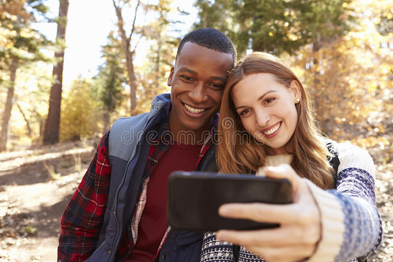 Smiling mixed race couple take a selfie in a forest royalty free stock photography