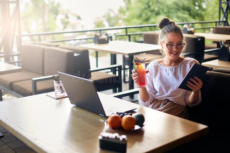 Smiling mixed race woman with cocktail in hand works with laptop. Businesswoman in glasses drinks juice for body stock photography