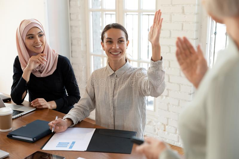 Smiling mixed race young female teammate raising hand. stock image