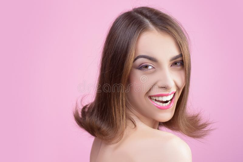 Smiling model with perfect make-up. Amazing smile. woman. White teeth. Healthy teeth. Young girl in studio on pink. Background. Close-up portrait stock image