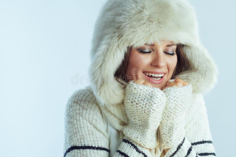 Smiling modern middle age woman warming hands with hot breath stock image
