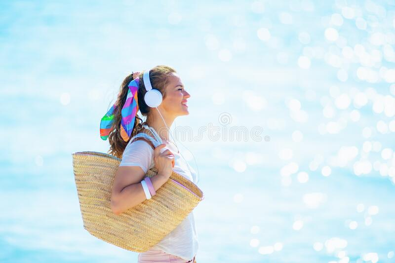 Smiling modern woman listening to music on seacoast stock photos