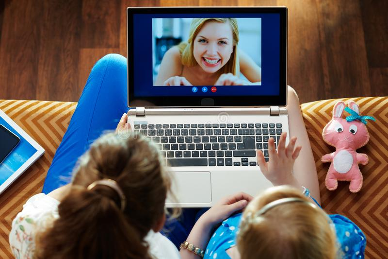 Mother and child using computer for video call on laptop. Smiling modern mother and child sitting on sofa in the modern living room using computer for video call stock photography