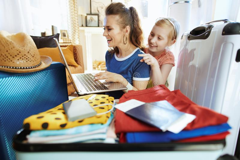 Smiling modern mother and child travellers buying plane tickets. Smiling modern mother and child travellers at modern home in sunny summer day buying plane stock photo