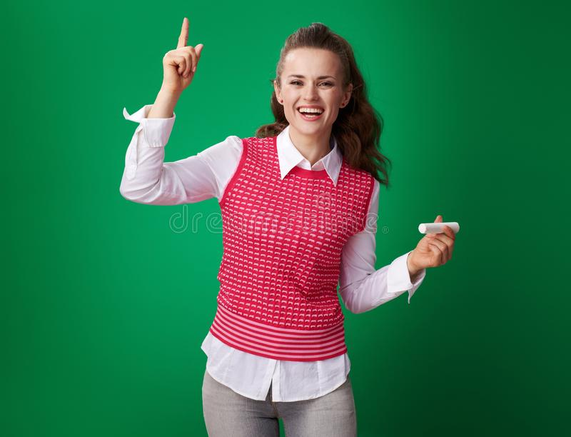 Smiling modern student woman with piece of chalk got idea. Smiling modern student woman in a red waistcoat with a piece of chalk got idea on green background stock image