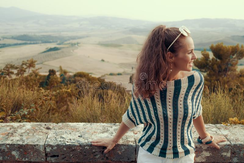 Smiling modern tourist woman looking into distance royalty free stock photo