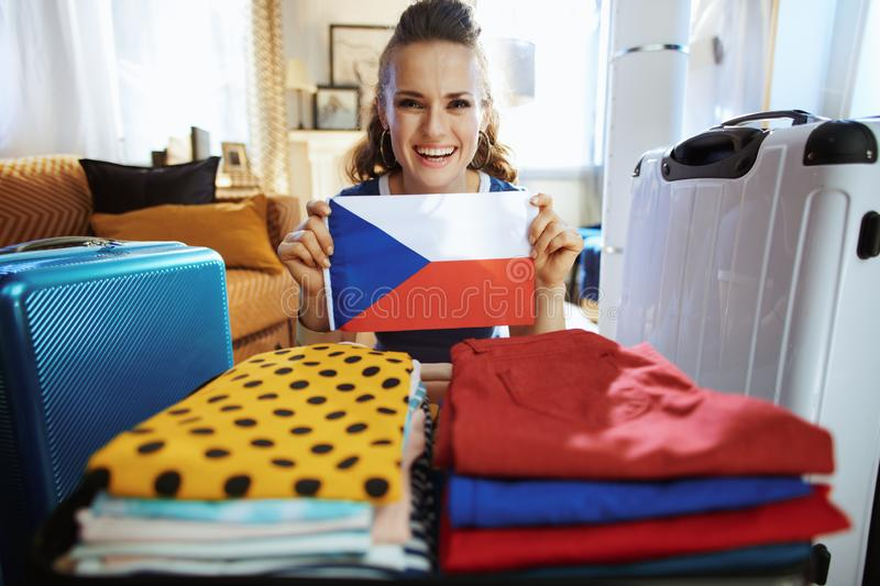 Smiling modern traveller woman showing Czech flag stock image