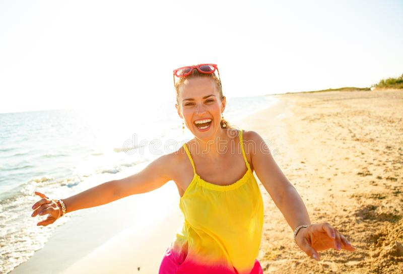 Smiling modern woman on beach in evening having fun time. Colorful and wonderfully cheerful mood. Portrait of smiling modern woman in colorful dress on the beach stock photography