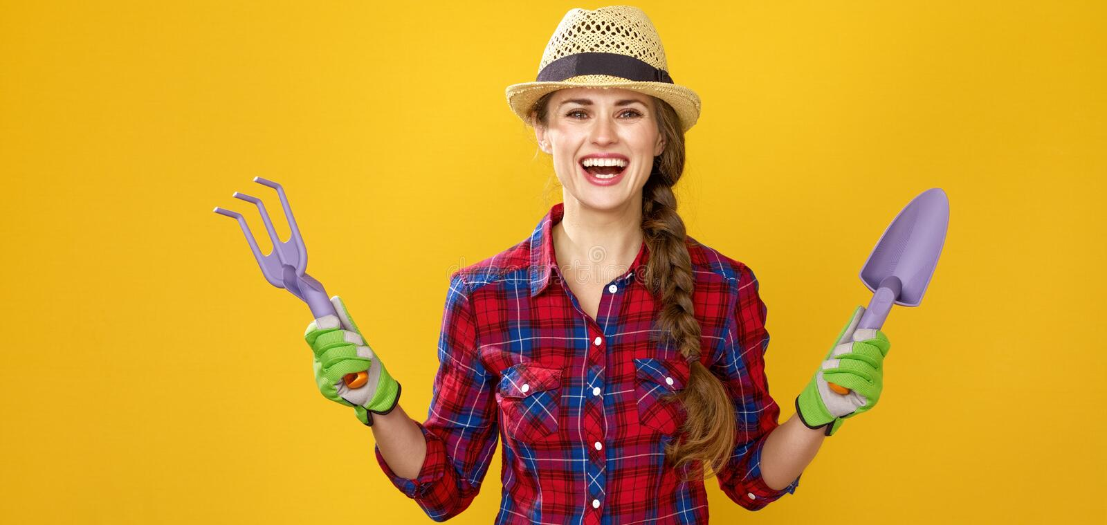 Smiling modern woman farmer showing gardening tools stock photo