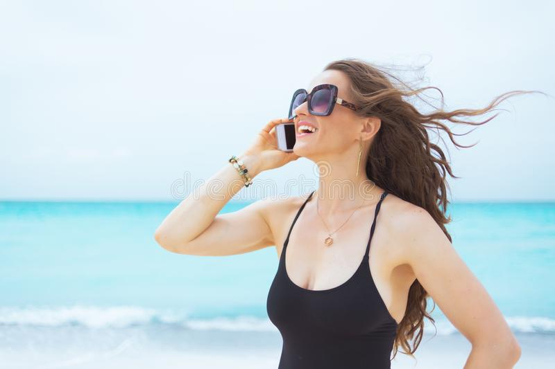 Smiling 40 year old woman on white beach speaking on cell phone royalty free stock photos