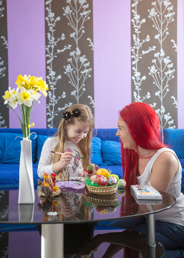Smiling mom and daughter kid paint Easter eggs stock images