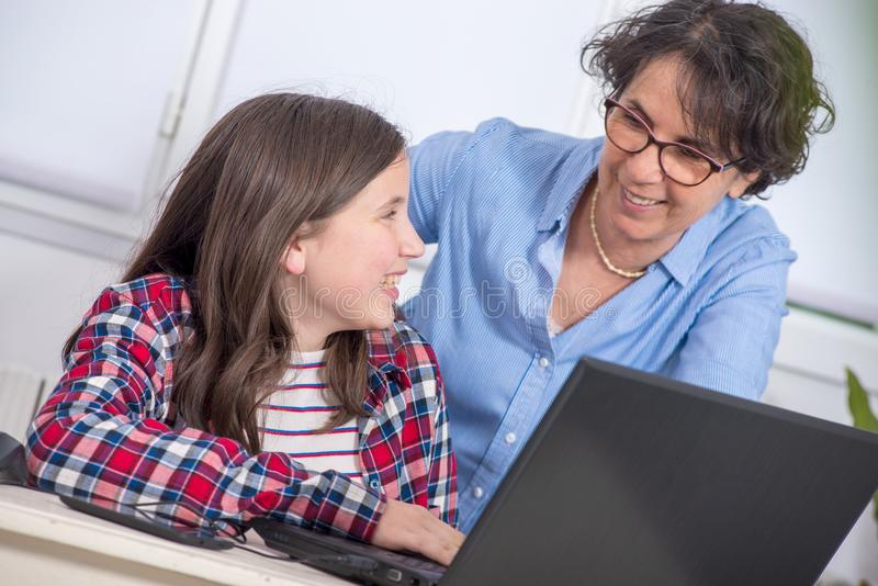 Smiling mom and daughter using laptop at home. Smiling mom and daughter using a laptop at home stock images
