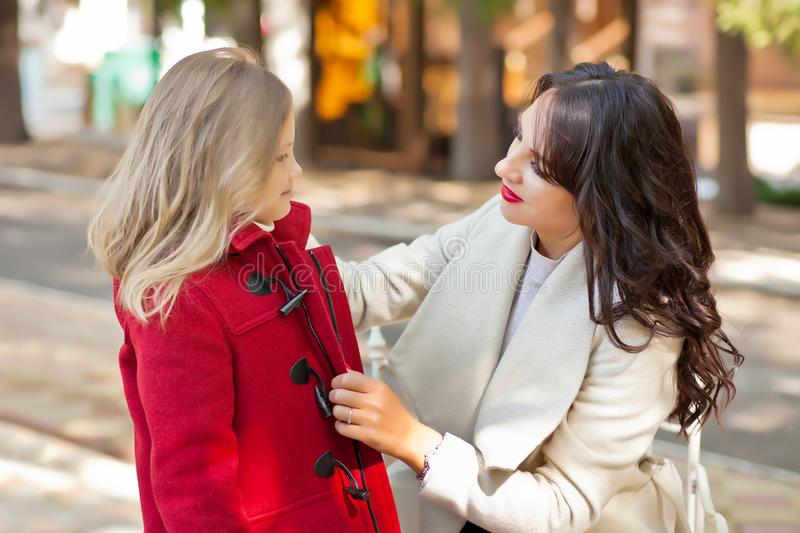 Smiling mom helps little cute daughter fasten her red coat royalty free stock photos