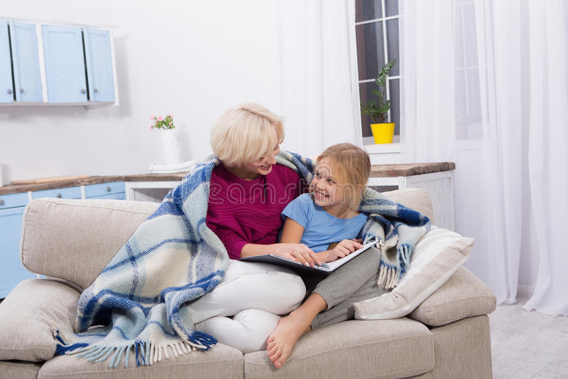 Smiling mom and her sick daughter staying at home, reading books. Mother taking care of her child while illness royalty free stock photo