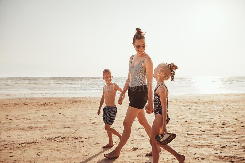 Smiling Mom and her kids walking along a sandy beach stock photography