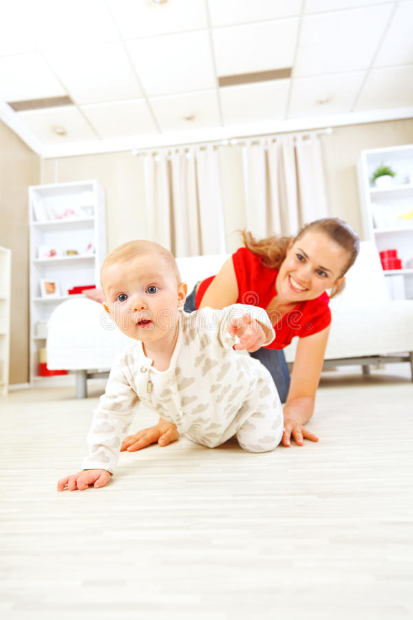 Smiling mommy playing with creeping on floor baby. Mommy playing with creeping on floor baby stock photos