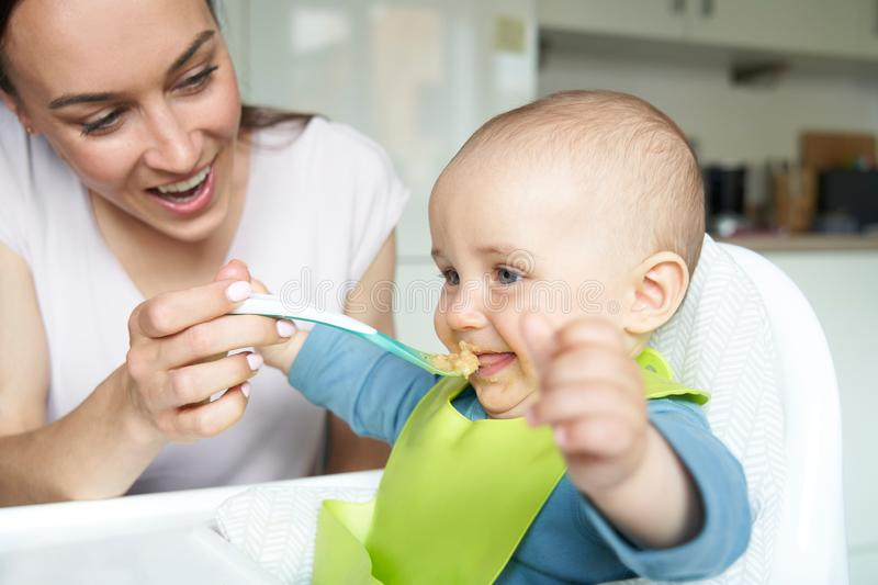 Smiling 8 Month Old Baby Boy At Home In High Chair Being Fed Solid Food By Mother With Spoon royalty free stock photos
