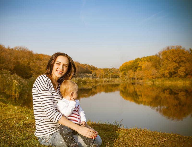 Smiling mother and baby on autumn lake stock images