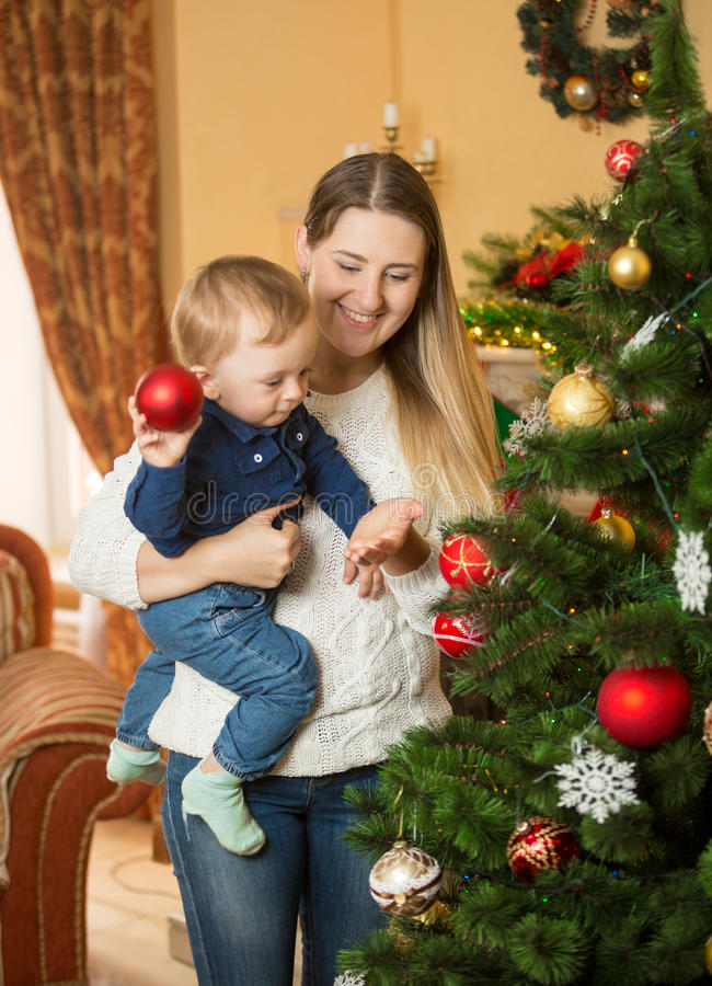Smiling mother and baby boy decorating Christmas tree with baubles royalty free stock photos