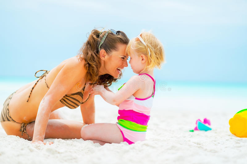 Smiling mother and baby girl playing on beach. Portrait of smiling mother and baby girl playing on beach royalty free stock image