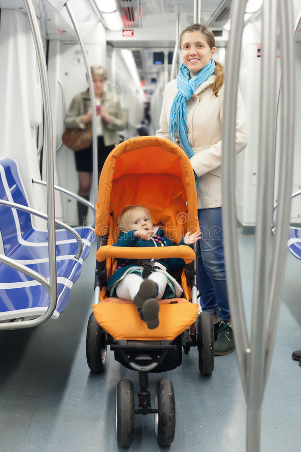 Smiling mother with baby at metro. Smiling mother with baby in stroller at metro stock image