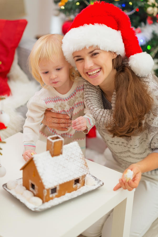 Smiling mother and baby near Gingerbread House stock photos