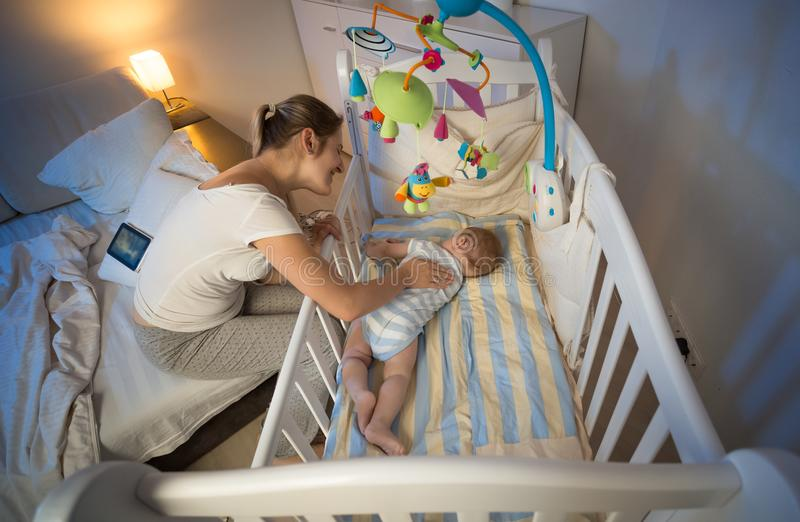 Beautiful smiling mother caressing her baby son lying in crib at night. Smiling mother caressing her baby son lying in crib at night stock photo