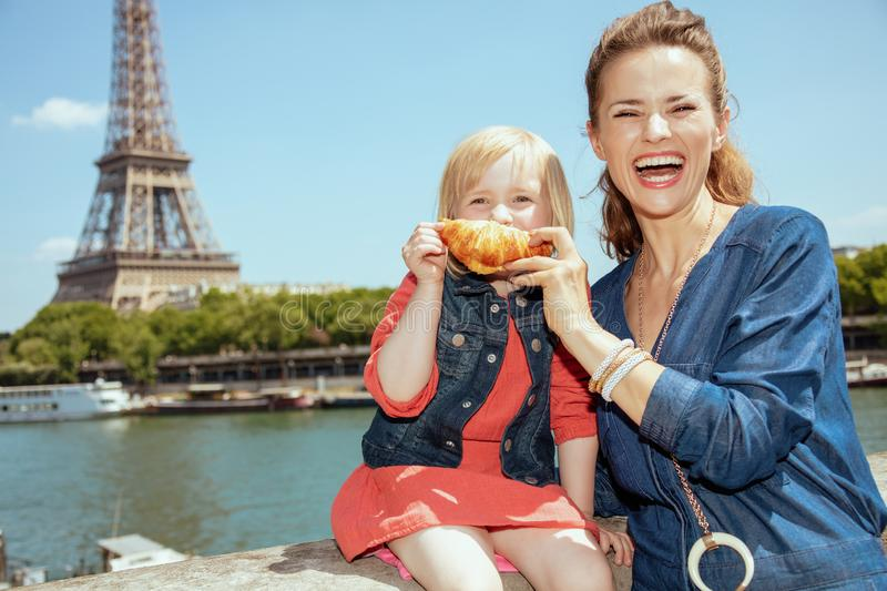 Smiling mother and child travellers making smile with croissant royalty free stock photo