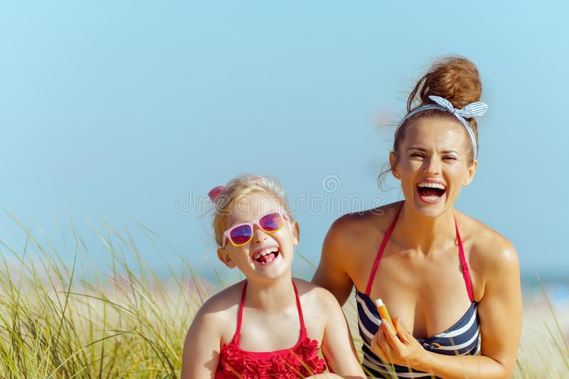 Smiling mother and child use lipstick with spf on seacoast stock images
