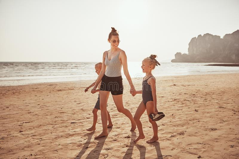Smiling Mother and children walking together along a sandy beach stock photography