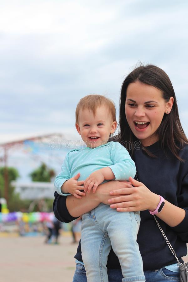 smiling mother with cute baby in her arms outdoors stock photo