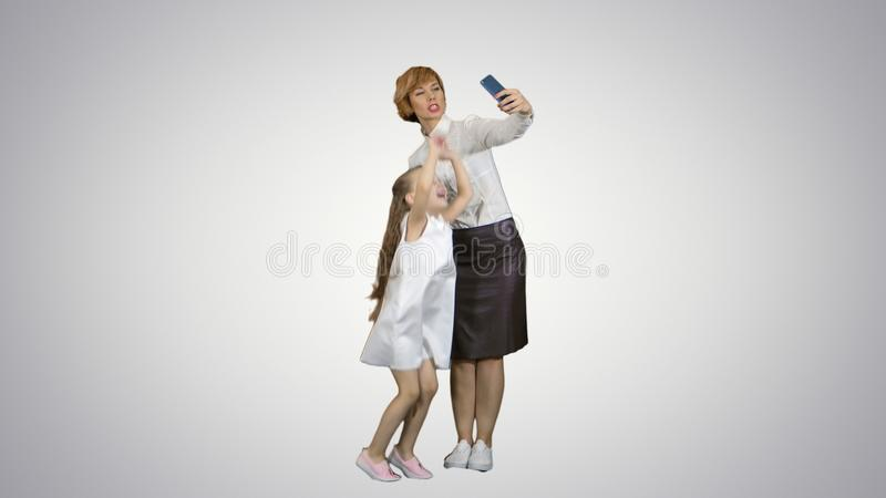 Smiling mother and daughter bonding together to take a selfie on white background. Professional shot in 4K resolution. 095. You can use it e.g. in your stock photos