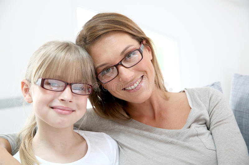 Smiling mother and daughter at home stock image