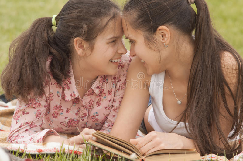 Smiling mother and daughter lying outdoor stock photo
