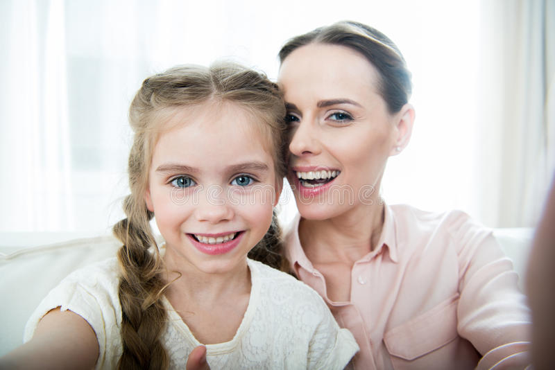 Smiling mother and daughter making selfie stock photo