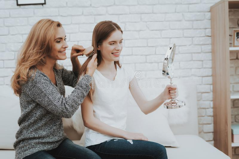 Smiling Mother and Daughter with Mirror on Sofa. royalty free stock images