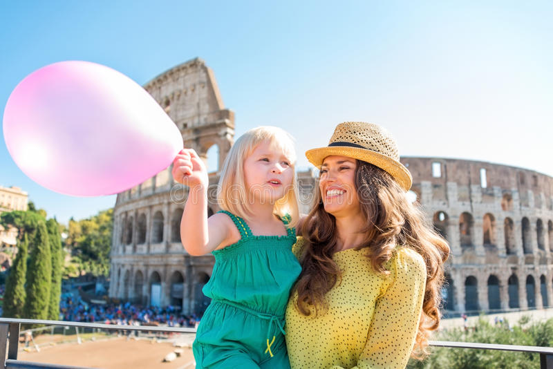 Smiling mother and daughter with pink balloon by Colosseum. A brunette mother wearing a hat in the summer in Rome is holding her blonde daughter, who is waving a stock photo