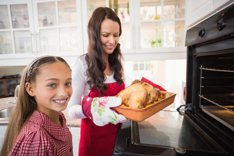 Smiling mother and daughter with roast turkey stock photo
