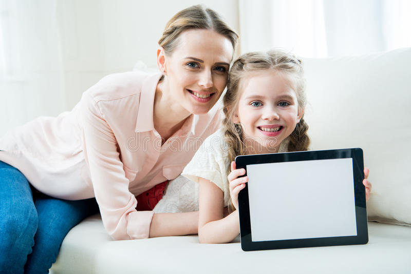 Smiling mother and daughter showing digital tablet stock photos