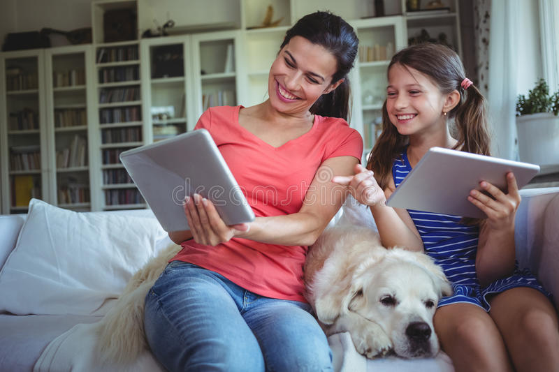 Smiling mother and daughter sitting with pet dog and using digital tablet royalty free stock photography