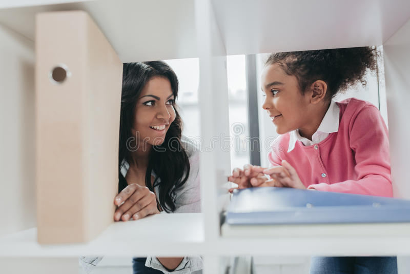 Smiling mother and daughter standing near bookshelves and smiling each other royalty free stock photography
