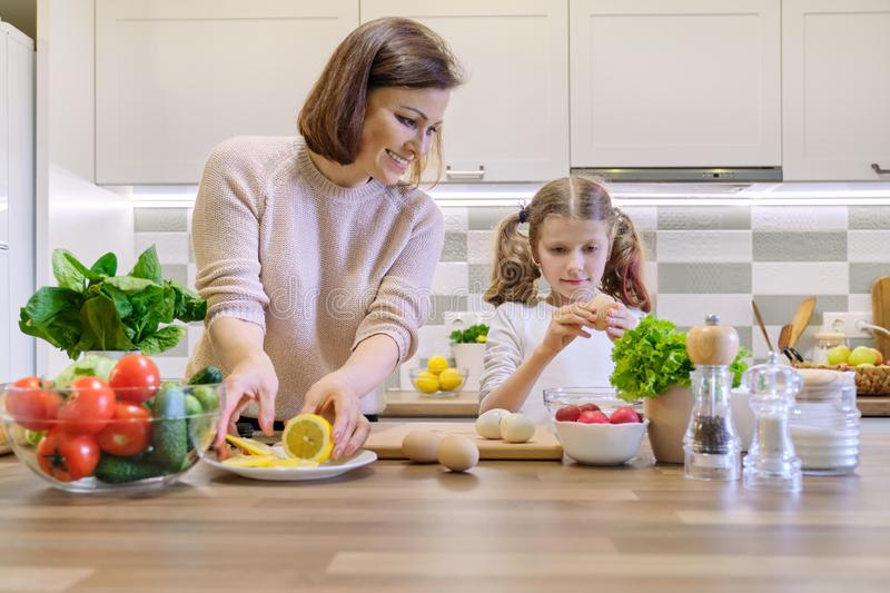 Smiling mother and daughter 8, 9 years old cooking together in kitchen vegetable salad. Healthy home food, communication parent royalty free stock photography
