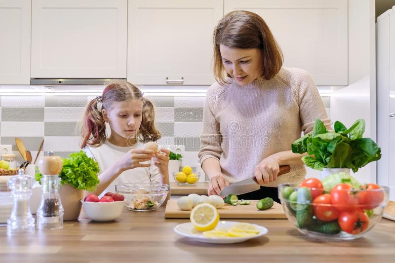 Smiling mother and daughter 8, 9 years old cooking together in kitchen vegetable salad. Healthy home food, communication parent royalty free stock photos