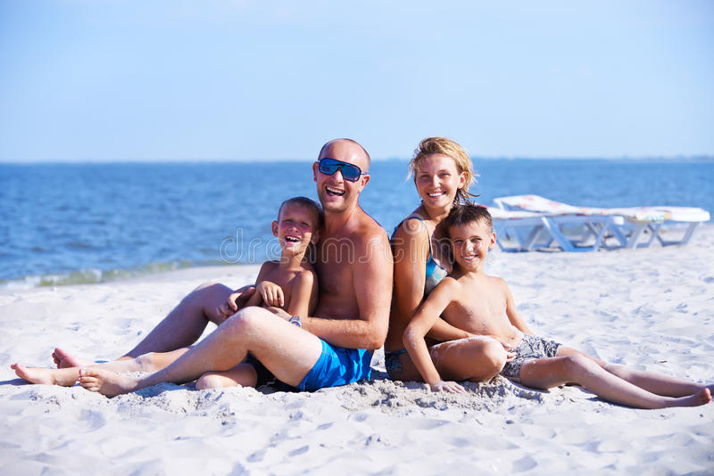 Smiling mother and father with children on the beach. Happy smiling mother and father with two children sitting on the sunny beach stock image
