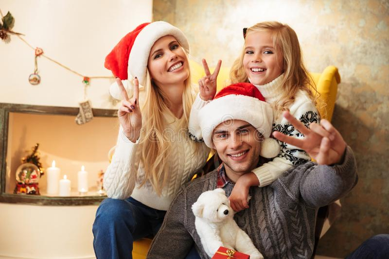 Smiling mother, father and daughter showing peace sign, looking stock photo